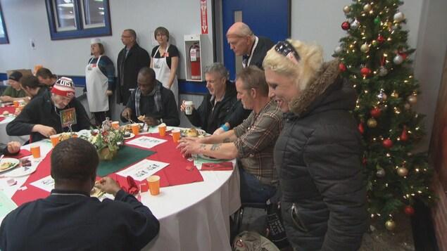 Des gens en train de manger alors qu'ils sont assis à une table dans un local de la Mission d'Ottawa.