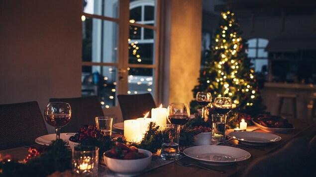 Une table est décorée de bougies, de branches de sapin et de canneberges, à côté d'un sapin de Noël illuminé