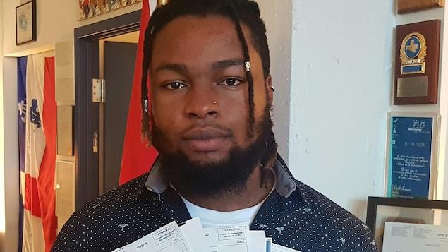 Représenté par le Centre de recherche-action en relations raciales, Stanley Jossirain poursuit la ville et la police de Repentigny pour 200 000$. Sur la photo il tient une liasse de contraventions reçues en 2018.