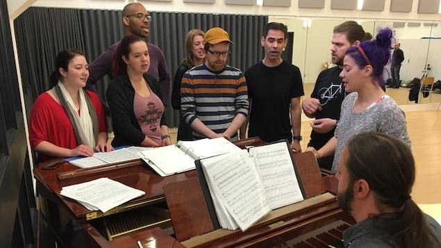 Des chanteurs accompagnés d'un pianiste lors d'une répétition