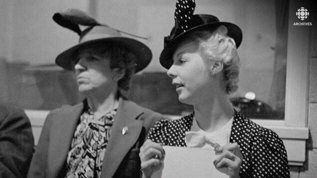 Assises dans un studio de radio, les comédiennes Jeanne Maubourg et Olivette Thibault, toutes deux portant un chapeau.