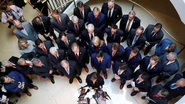 Vue de haut de la trentaine de républicains, majoritairement des hommes, à l'entrée de la salle où se déroulent les enquêtes.