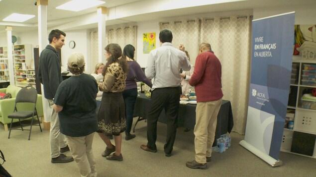 Vue sur huit personnes qui sont debout dans une salle. Ils discutent ensemble autour d'une table sur laquelle il y a de la nourriture.