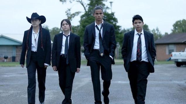 Quatre ados autochtones marchent en complet au milieu d'une rue.