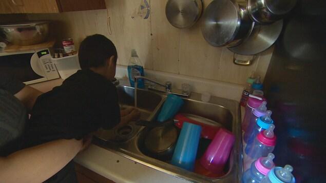 Un Autochtone de 4 ans se lave les mains dans l'évier de la cuisine.