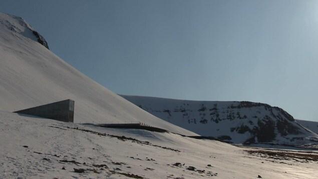 Un pic de béton sort d'une montagne enneigée sous le soleil.