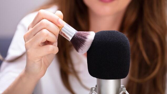 Une femme utilise un pinceau sur un micro.