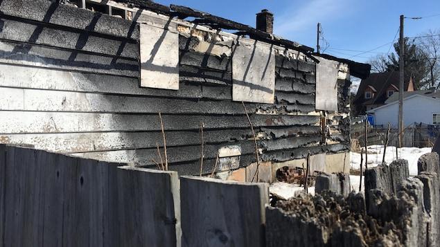 Vue de côté d'une maison sinistrée, noircie par les flammes.