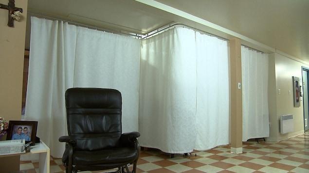 Des rideaux sont installés sur un rail accroché au plafond. Ils servent de murs de séparation pour délimiter les chambres de certains résidents d'une maison pour aînés.