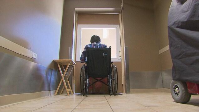 Un résident parle avec l'un de ses proches à travers une porte en plexiglas.