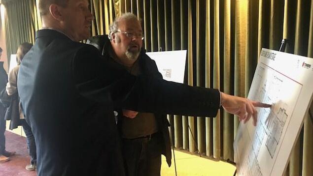 Un homme montre du doigt le plan d'un projet immobilier un tableau alors qu'un autre écoute