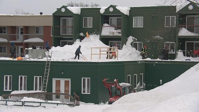 Des travailleurs déneigent un toit à Lévis