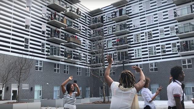 Des personnes âgées sur des balcons et de jeunes gens sur un parterre dansent au rythme de la chanson Let's Twist Again.