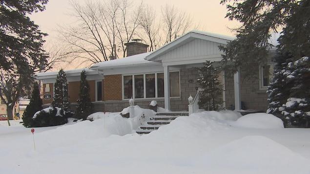 La façade extérieure de la résidence en hiver, avec de la neige.