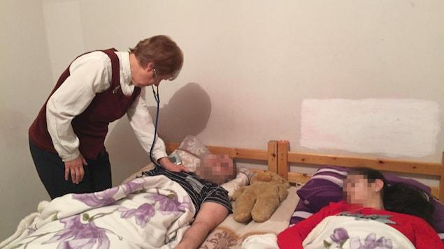 Une femme docteure examine Kostan et Miléna, deux enfants victimes du « syndrome de résignation », un mal surtout présent en Suède. Les deux enfants sont couchés dans un lit, mais ils ne dorment pas; ils sont inconscients.
