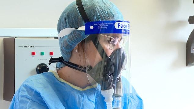 Une femme porte le respirateur dans une clinique dentaire.