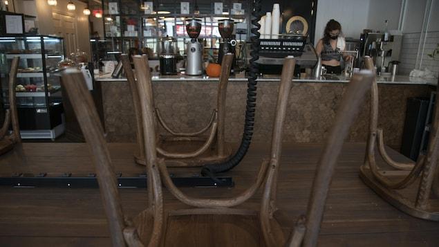 Des chaises disposées à l'envers sur une table dans un café.