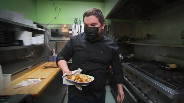 Un des chefs qui tient un plat dans la cuisine du restaurant.