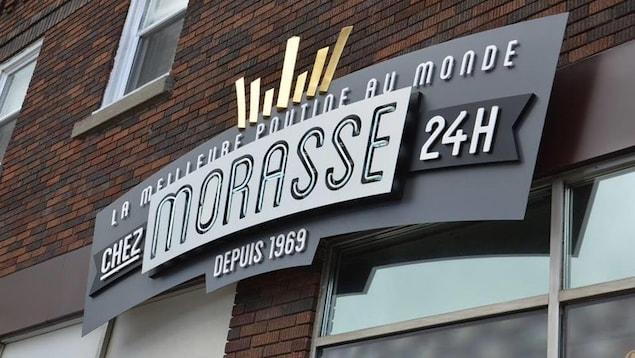 Une enseigne de casse-croûte indique «Chez Morasse, 24h, depuis 1969, la meilleure poutine au monde».