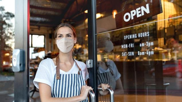 Une femme portant un masque ouvre la porte d'un café.