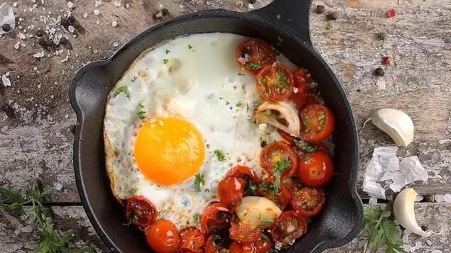 Une poêle en fonte avec un oeuf et des tomates cerises confites.