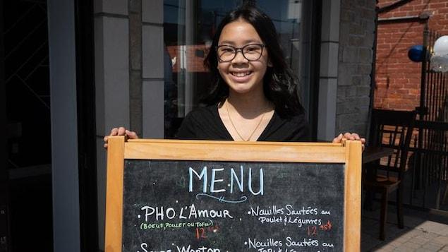 Une adolescente souriante montre le menu de l'établissement, debout devant le restaurant situé à Gatineau.