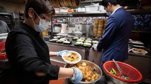 Des cuisiniers portant des masques préparent des plats pour emporter.