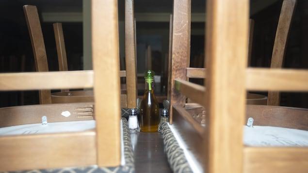 Une bouteille d'huile sur une table sur laquelle on a déposé des chaises à l'envers.