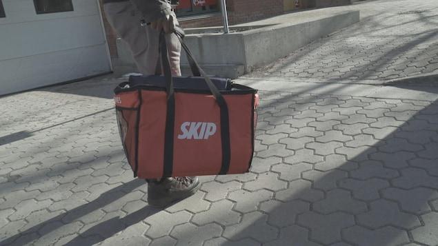 Un homme se dirige vers un restaurant avec un sac Skip the dishes.