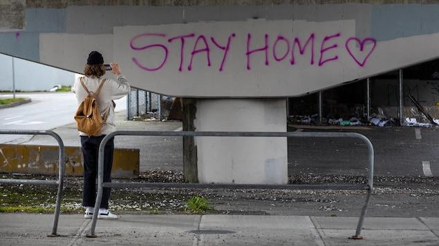 Une fille sous un pont prend en photo le graffiti.