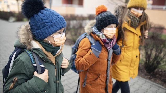 Trois jeunes d'âge différents marchent vers l'école avec des sacs à dos. Ils portent chacun un masque non médical et sont habillés pour le temps froid avec un manteau et une tuque.