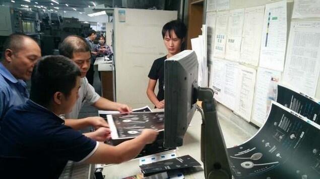 Des travailleurs regroupés autour d'un ordinateur.