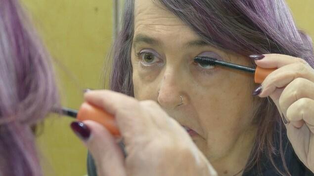 سيّدة تضع ماسكارا على رموشها.