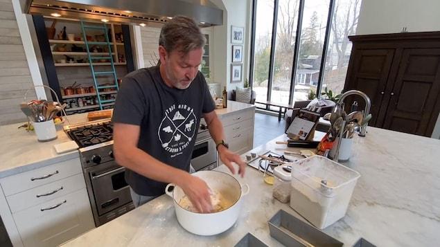 Ricardo manipule de la pâte à pain dans une grande casserole en fonte, sur son comptoir de cuisine.