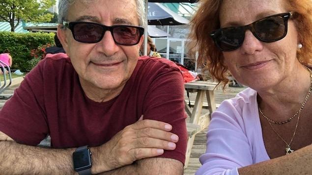 Le couple est souriant, sur une terrasse.