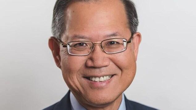 Richard T. Lee porte un costume cravate et des lunettes.
