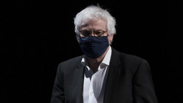 Le Dr Richard Massé, debout devant un fond noir.