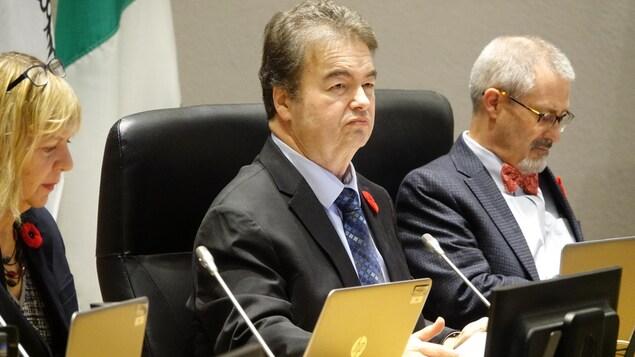 Rick Chiarelli assis à une table devant un ordinateur portatif dans la salle du conseil municipal d'Ottawa.