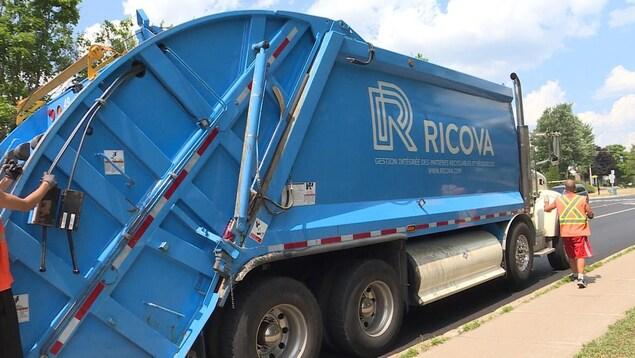 Un camion à ordures bleu.