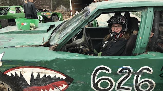 Une femme est assise dans une voiture numérotée 626. Elle porte un casque.