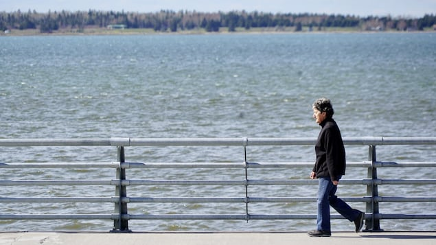 Une femme marche sur la Promenade de la mer, à Rimouski.