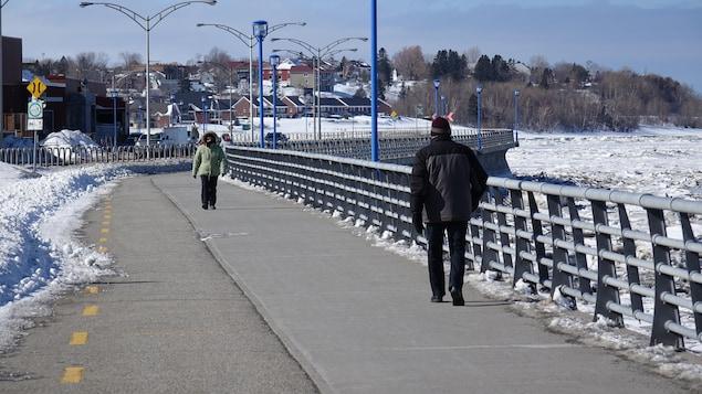Deux personnes marchent sur la Promenade, près du fleuve gelé à Rimouski.