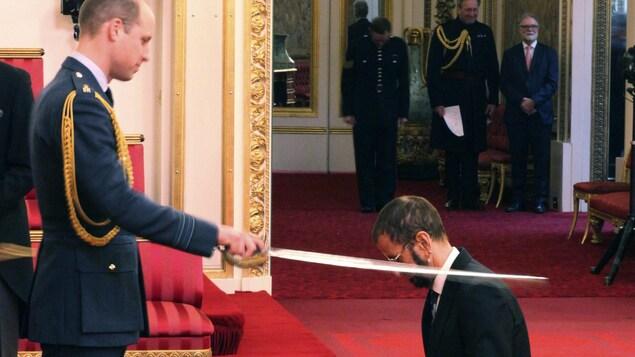 Ringo Starr se faisant adouber par le prince William.