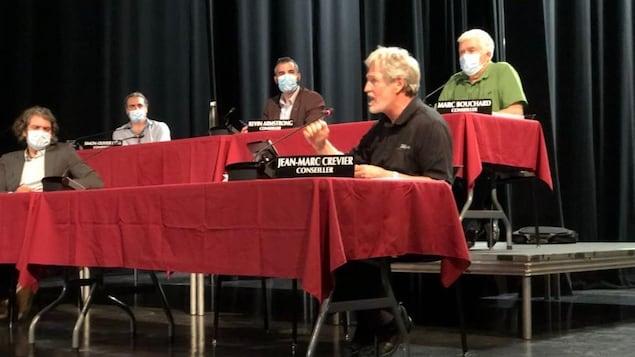 Jean-Marc Crevier est assis à une table rouge avec d'autres conseillers.