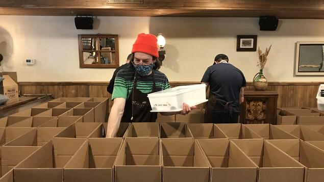 Un employé dépose des mets dans une boîte.