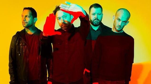 Quatre hommes vêtus de noir sur fond jaune.