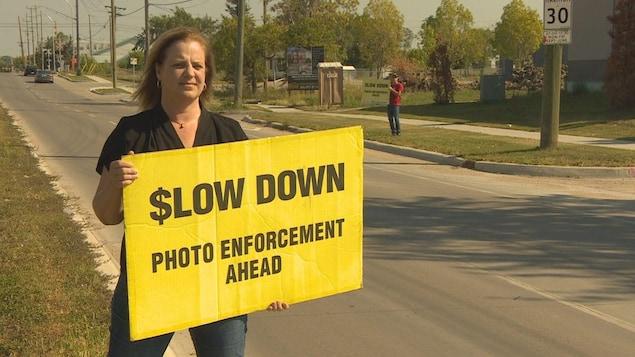 Une femme qui tient une affiche jaune sur laquelle on lit (en anglais) : ralentissez, photo radar devant. En arrière-plan, on voit la rue et un autre homme avec un affiche semblable.