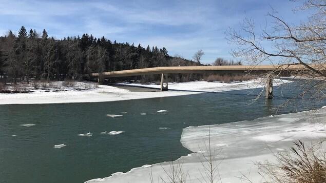 Une rivière. Les rives sont gelées. Un pont enjambe le cours d'eau. On aperçoit un bois dans le fond. Le ciel est bleu.