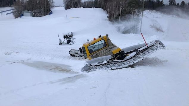 Une dameuse enfoncée dans la glace.