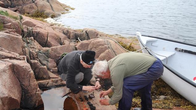 Deux archéologues analysent des fragments de tuiles sur la berge d'une rivière.